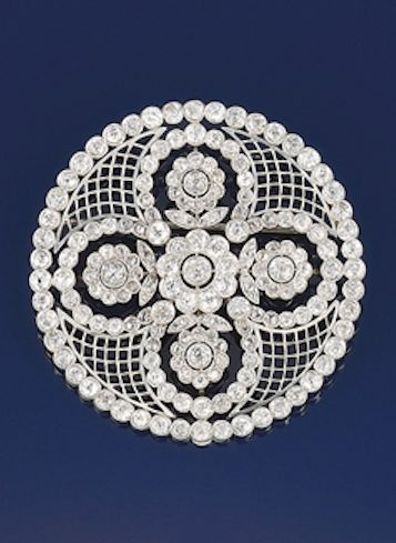 A Belle Epoque platinum and diamond cluster rosette brooch Designed as a central quatrefoil of diamond circular cluster flowerheads with diamond line border and trelliswork detail, circa 1905, fitted case: