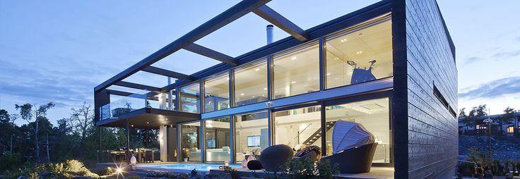 Custom Home II on moderni hirsitalo, jossa lasi yhdistyy massiiviseen seinärakenteeseen.