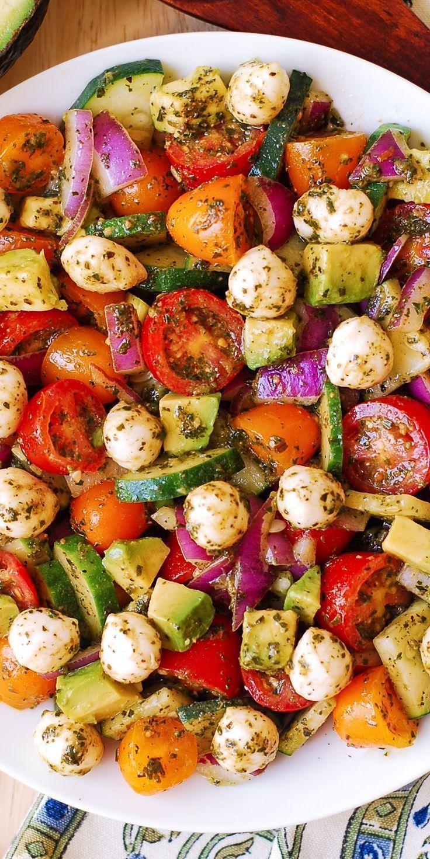 Avocado-Salat mit Tomaten, Mozzarella, Gurke, roten Zwiebeln und Basilikumpesto mit Zitronensaft