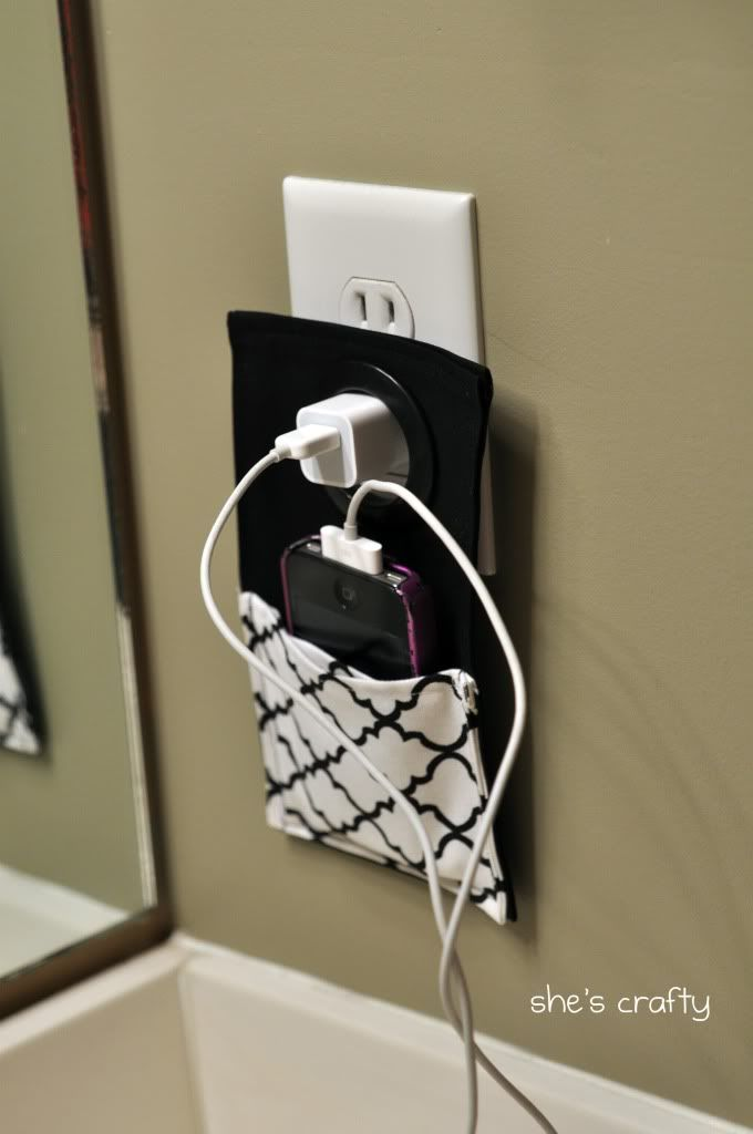 "She's crafty: gift ideas ""I saw a cute cell phone holder on pinterest and it gave me the idea to make one for my sister in law. From my stash, I used black fabric for the back, stregthened with heat and bond and quatrafoil fabric for the pocket. I sewed all the way around everything. Then I took a large grommet (for curtains) and put it through the top where it hangs onto the charger. After I took this picture I added some black ric rac to the top of the pocket to finish the edge"""