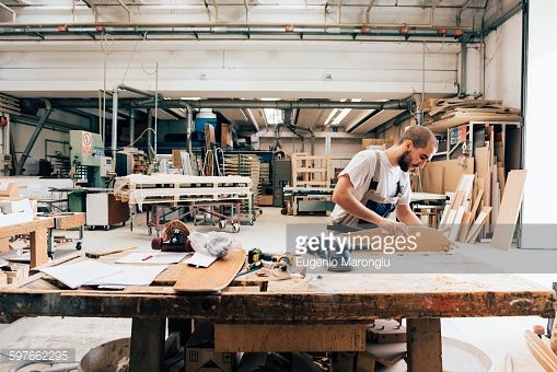 Stock Photo : Young man in carpentry workshop looking down sanding skateboard