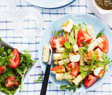 Vegetarisk pastarätt med pesto blandad med crème fraiche till en krämig sås i vilken pastan blandas. Serveras med tomat- och ruccolasallad samt knaperstekt halloumi.
