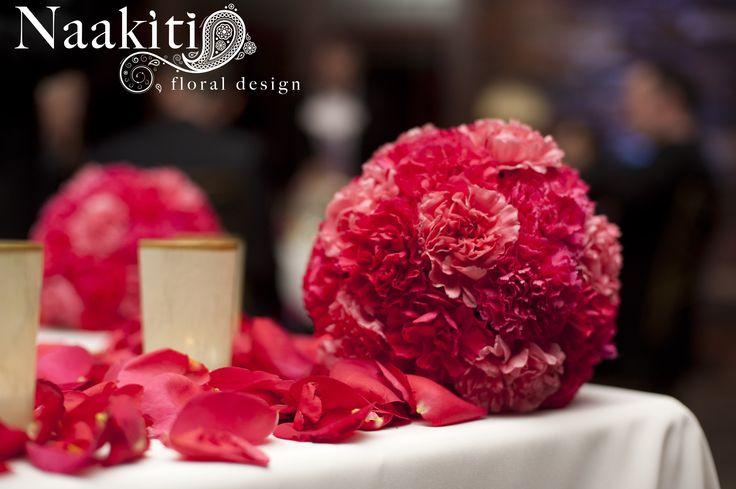 Pink pomander balls at the head of the sweetheart table. #NaakitiFloral #PomanderBalls #PinkWedding #Flowers