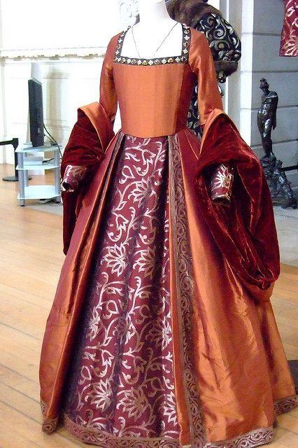 Abito arancio in seta con piccole pietre dure sulla scollatura; la sottogonna è in damasco viola e argento.Sovramaniche in velluto. Costo £230