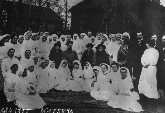 1915 - Le tsar (Nicolas II) avec sa famille dans un hôpital militaire sur le front, le tsar à côté de sa fille, la grande duchesse Olga, à côté de la tsarine la grande duchesse Tatiana (entourés d'infirmières) : photographie de presse / Agence Rol