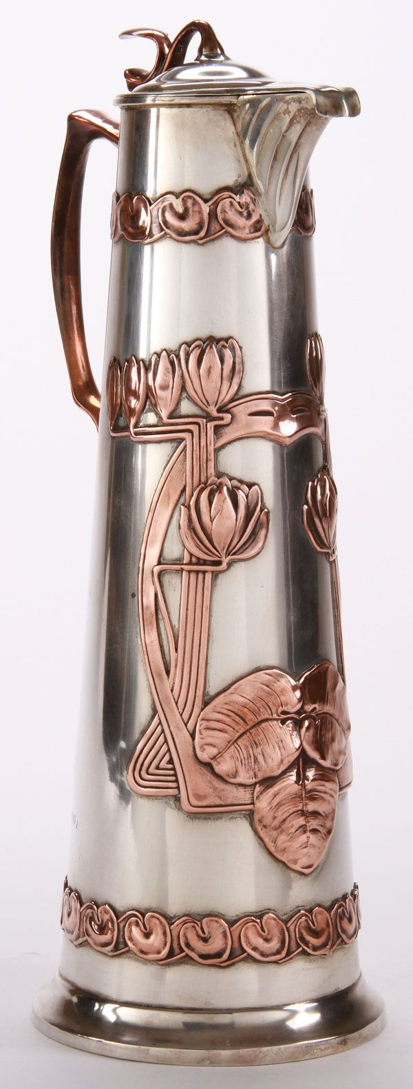 A LARGE AND IMPRESSIVE RUSSIAN SILVER ART NOUVEAU WINE CARAFE, 1ST ARTEL, MOSCOW, 1908-1917. Of tapered cylindrical form, the base banded with copper plated lily leaves and the front with raised Art Nouveau design of water lillies. With hinged lid and copper plated handle. Verso with dedicatory inscription dated 1910. Hallmarked Moscow 1908-1917, and with Cyrillic maker's mark of the 1st Artel and 84 silver standard.