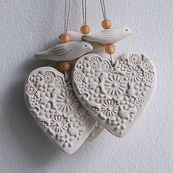 Ein Semi-Porzellan-Wand-hängen. Herz und hand geformten Vogel. Das Herz hat mit Blumenschmuck beeindruckt gewesen und der kleine Vogel hat eingeschnittene Flügel und Augen. Zwei kleine Glasperlen sind zusammen mit dem Herzen und Vogel auf Baumwollschnur aufgefädelt. Herz Größe ca. 6cm über