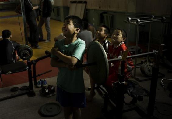 Children watch Mongolia's Olympic freestyle 60kg wrestler Mandakhnaran Ganzorig limber up at a wrestling gymnasium in Ulan Batur October 27, 2011.  REUTERS/Kieran Doherty