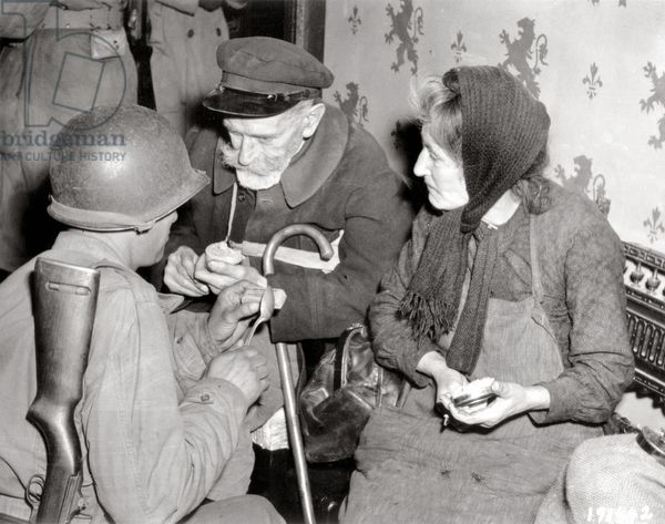 Two days after the liberation of the city, Eugene and Honorine Sérée, have just returned from Douville. 11th July 1944. They are looking for a place to stay. They get boxes with U.S. soldier rations and Bill W. Lemak from San Francisco, is offering them a piece of chocolate. The ruined city was liberated after heavy fighting on July 9 by the 79th Infantry Division. La Haye-du-Puits, Normandy, France.