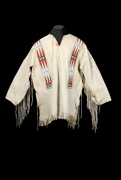 """Assiniboine Beaded Hide War Shirt, likely from Fort Peck, Montana, thread- and sinew-sewn with beaded panels overlaid along shoulders and chest using bead colors of cranberry, cobalt, greasy yellow, and white to create an elongated feather design; length 33"""" x chest 48""""."""