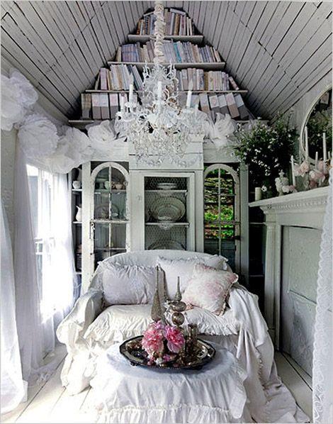 Cabaña blanca en el campo. Interior abuhardillado, alacena, sofá blanco y lámpara de araña