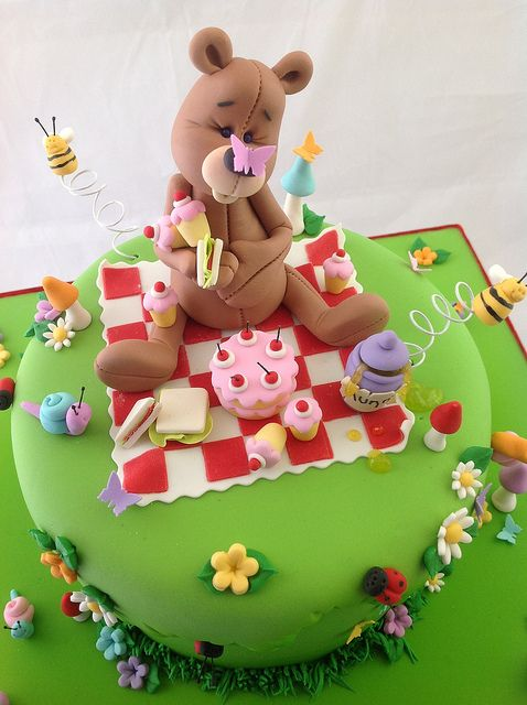 A truly inspiring birthday cake decorated with a teddy bear sat having a picnic.