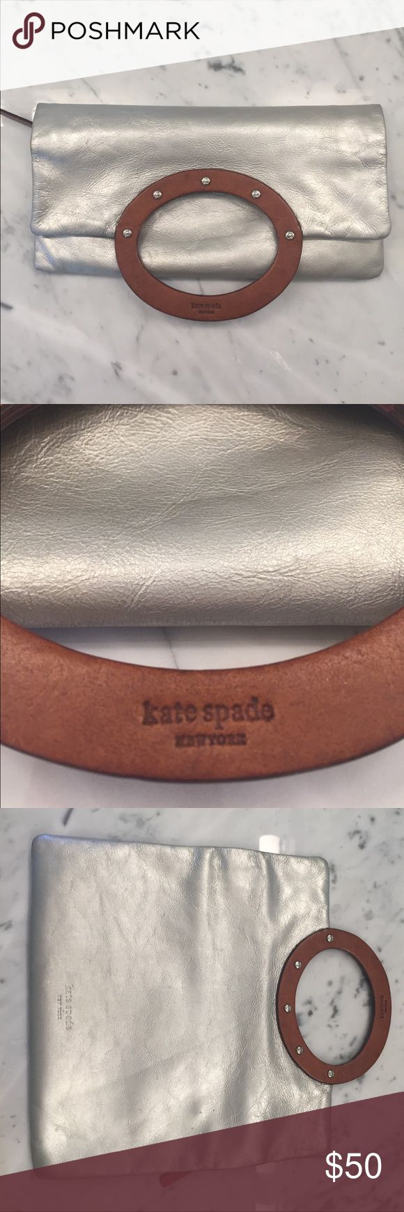 """Silver Kate Spade Clutch This adorable metallic clutch makes any outfit. It has a zipper on one side and folds in half, or you can hold it by the round wooden handle. Some small signs of wear - there is a mark on the zipper side (pictured) which is barely noticeable, especially when the clutch is folded and carried. Lots of room inside with one side pocket. Measures 10"""" when lying flat, 6"""" folded. kate spade Bags Clutches & Wristlets"""
