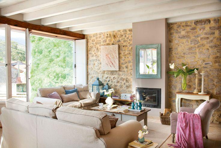 Salón rústico contemporáneo con pared de piedra, vigas en blanco y chimenea