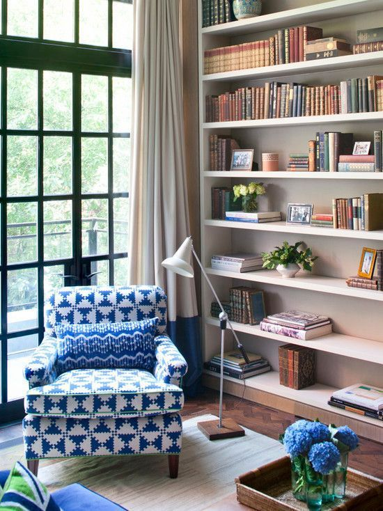 Floor-to-ceiling windows and bookshelves, plus a comfy chair and dedicated floor lamp, make for an idyllic reading nook.