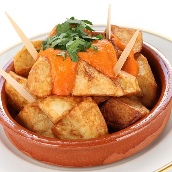 Patatas bravas are fried potato dices served with salsa brava, a spicy tomato sauce and are a common Spanish tapa