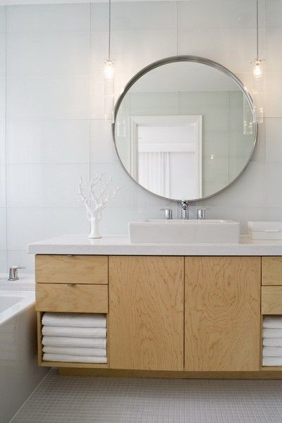 Nice cabinets and white counter, but don't like the sink or the round mirror