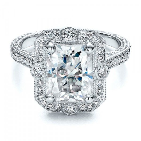 #100091 This beautiful engagement ring was custom designed for a client by Joseph Jewelry.A radiant cut center stone is accented by a halo of bright cut set...