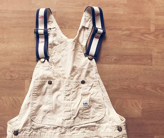 """Vintage white Lee painters overalls. Such a unique, hard to find color and size! Red, white, and blue colored suspenders, lots of fun pockets, and tons of character! These overalls are a lighter weight white cotton canvas material. Measures approximately waist 34"""" Hips 43"""" Marked"""
