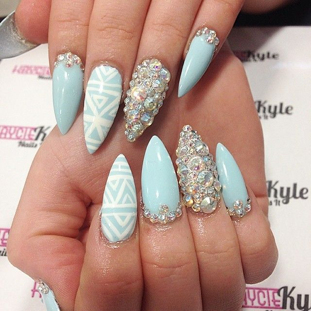 stiletto baby blue nails with designs on each nail.