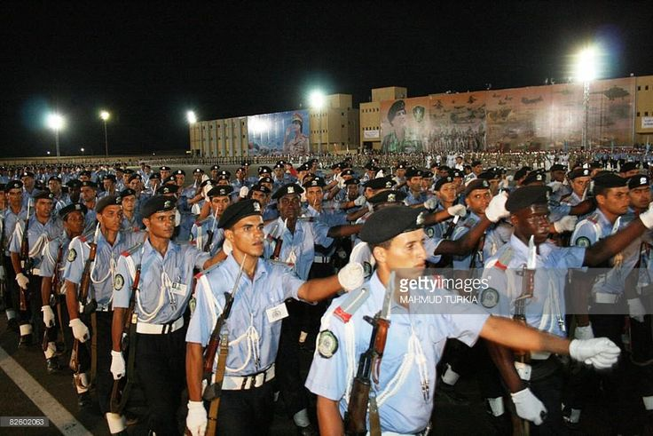 Libyan military graduates parade in front of giant mural portraits (background) of Libyan leader Moamer Kadhafi during the 'Fateh' ceremony in the Mediterranean city of Benghazi, east of Tripoli, on August 29, 2008 to mark the anniversary of the coup that Kadhafi to power almost four decades ago. Kadhafi took power after leading a military coup against King Idriss on September 1, 1969.