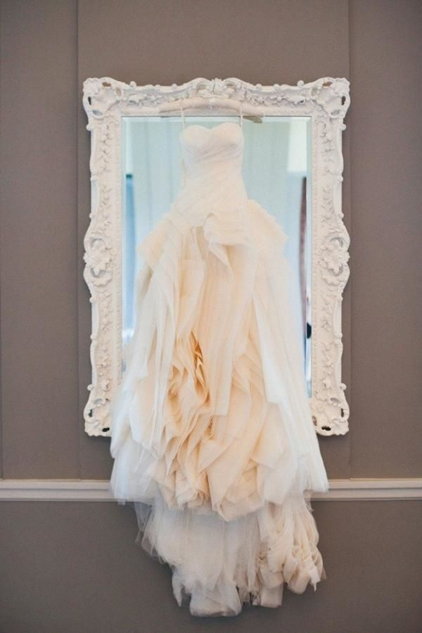 One of the more traditional photographs to add to your list is of the gown hanging in front of a mirror. It's a great way to show off all the details of your gown before all the hustle and bustle begins.
