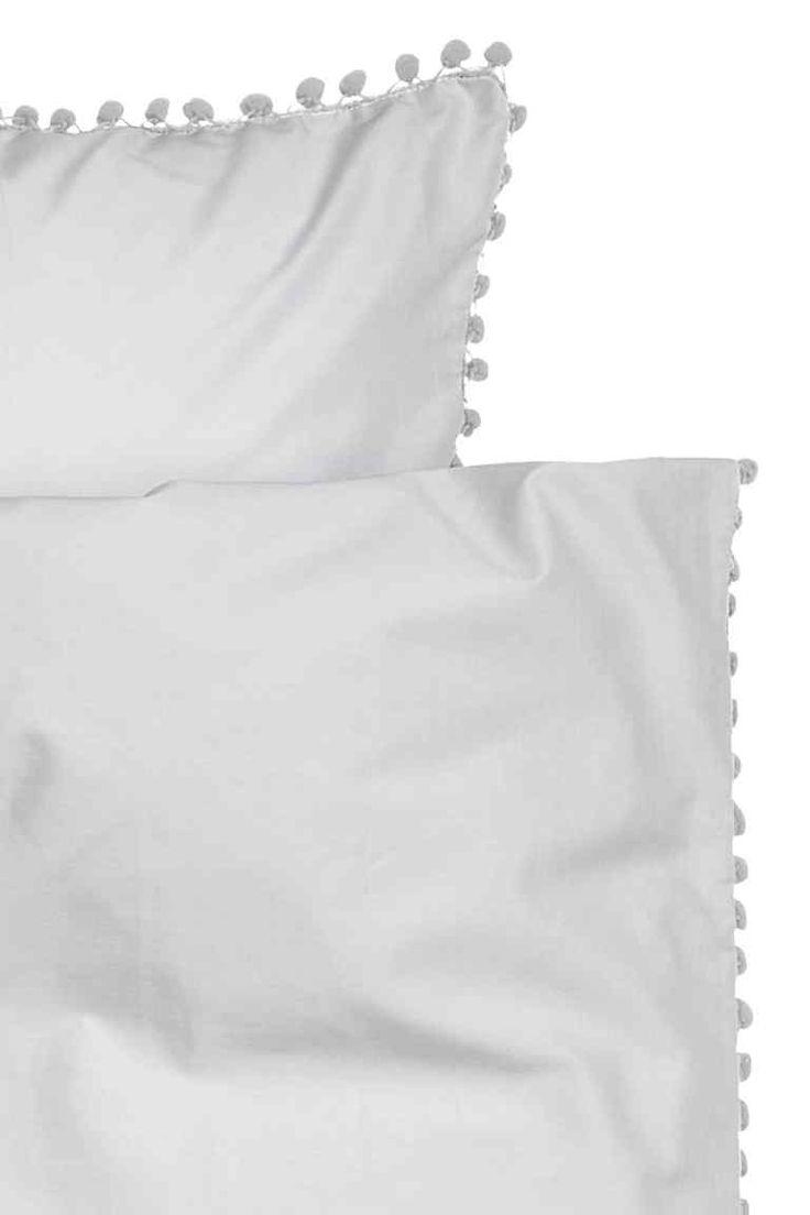 Set copripiumino con pon-pon: Set copripiumino a due piazze in sottile tessuto di cotone con pon-pon sui lati lunghi e su un lato corto. Bottoni automatici in metallo in basso. Due federe. Filo con titolo 30, numero di fili 144.