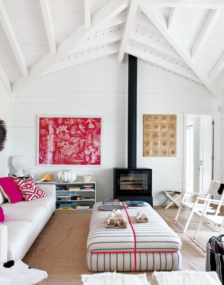 Ceiling beams in white living room with graphic artwork and bold prints