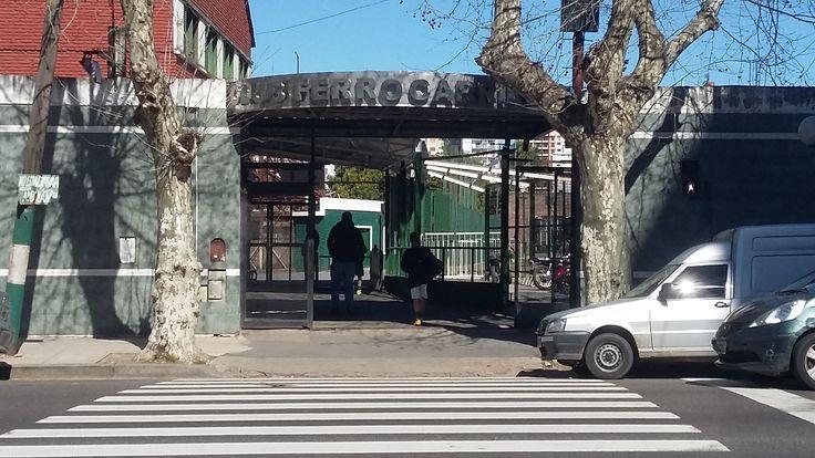 Podemos observar la entrada al Club Ferrocarril Oeste con gente entrando y saliendo constantemente.