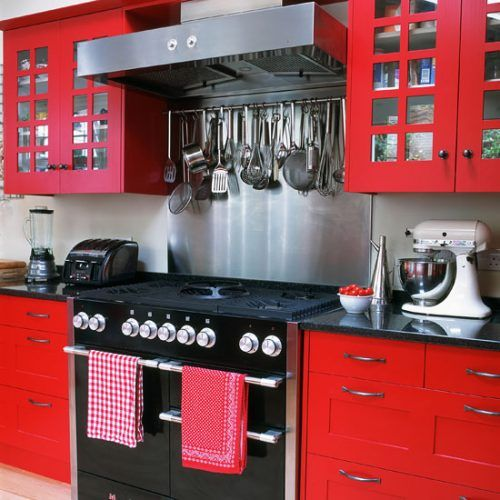 Small kitchen with red cabinetry, black granite worktop, black range cooker and stainless-steel splashback