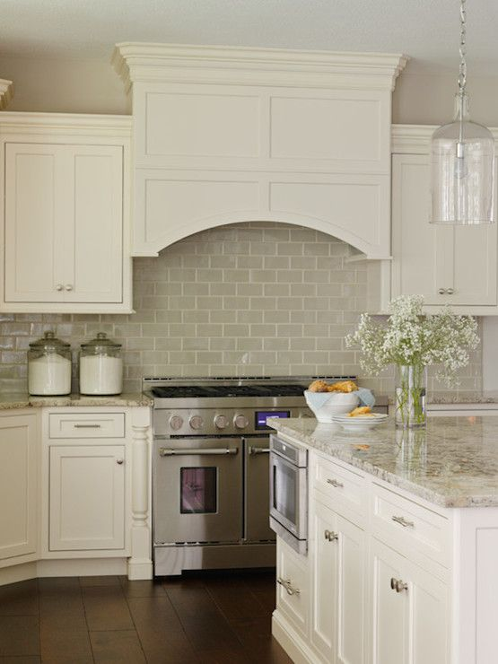 Gray Subway Tile Backsplash Under Ivory Cabinets And Curved Kitchen Hood,  Glass Jug Hanging Pendant