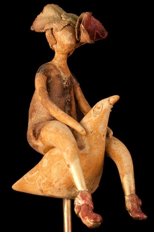 Mujer montando pájaro sobre soporte de hierro. Escultura. Decoración.