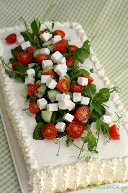 """this is a savory sandwich cake made with layered crustless sandwich bread, """"icing"""" (made with flavored cream cheese, sour cream, creme fraiche etc) and filled/topped with feta cheese, tomatoes, cucumbers etc."""