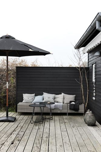 Horizontal privacy wall mimics siding of house. Scandinavian Retreat: 42 sqm summer house