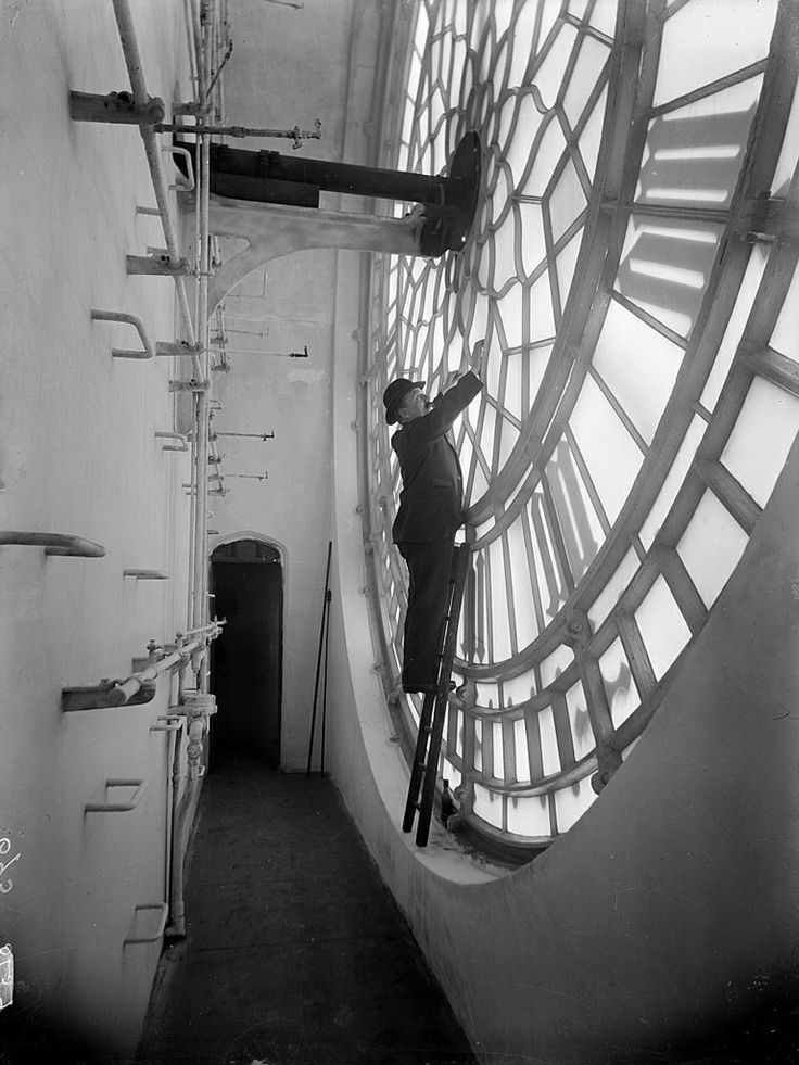 """Gentleman in bowler hat inspecting the clock in Elizabeth Tower in the Houses of Parliament, London, 1920′s [some call this photograph """"Inside the Big Ben"""", but Big Ben is the nickname for the Bell, not the entire clock]"""