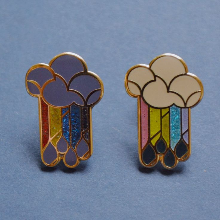 """Art deco influenced cloud, rainbow, and rain design. - Size: 1"""" tall x 1mm thickness - Sanded hardened enamel poured into cast metal, smooth to the touch"""