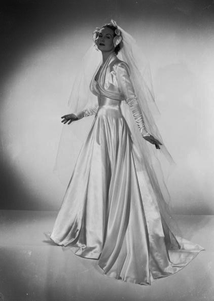 A satin wedding dress with long veil by Mercia, January 1952.