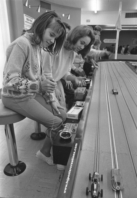 Girls challenge the boys at a hobby shop slot car track in the 1960's.