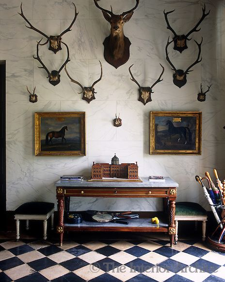 Sets of antlers are dsiplayed on the marbleised wall of the entrance hall ~ Chateau de Groussay