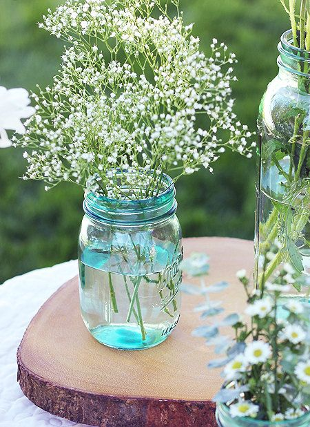 Here's the great thing about using handcrafted blue tinted mason jars as wedding centerpieces- they require very little effort to make them look BEAUTIFUL. Even just a hint of baby's breath, daisies, lilies, cheap roses, or flowers from your garden will do the trick & it will look fabulous. No spending money on ridiculously large extravagant flowers and vases and bouquets and rhinestones. You can spend less money on centerpieces and more elsewhere!  ORDER NOW through Etsy!