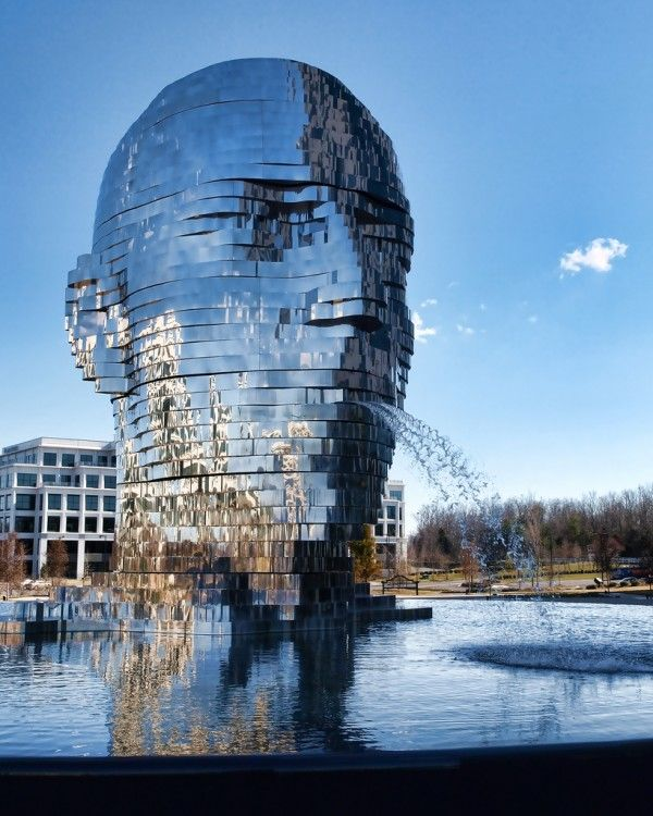 Metalmorphosis is a mirrored water fountain by Czech sculptor David Černý that was constructed at the Whitehall Technology Park in Charlotte, NC. The 14-ton sculpture is made from massive stainless steel layers that rotate 360 degrees and occasionally align to create a massive head. It even has it's own live webcam.