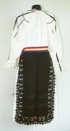 Romanian Women's costume from county of Sibiu  Black front and back aprons (catrinţe) made of a single width of black felted material. They have two rows of embroidery in black silk on the lower part, and an edging in black openwork with a row of crochet black lace on the sides and the front aporn has a fringe made of black silk thread on the hem. Pleated white cotton underskirt (poale) Narrow fabric belt (brâu) made of ribbon in the colours of the Romanian flag