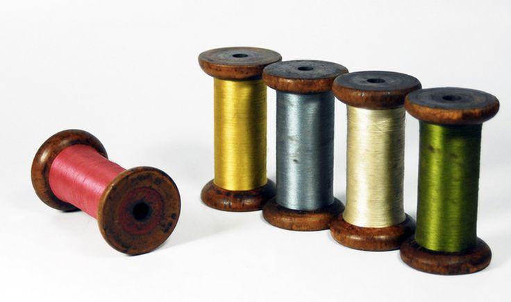 Spulwerk: Alte Holzspulen mit seidigen Garnresten