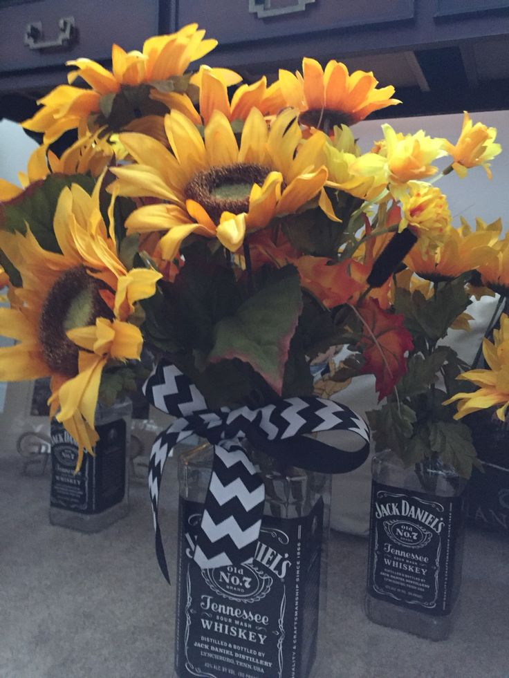 Large Jack Daniels bottle used for a centerpiece with sunflowers and black and white chevron ribbon