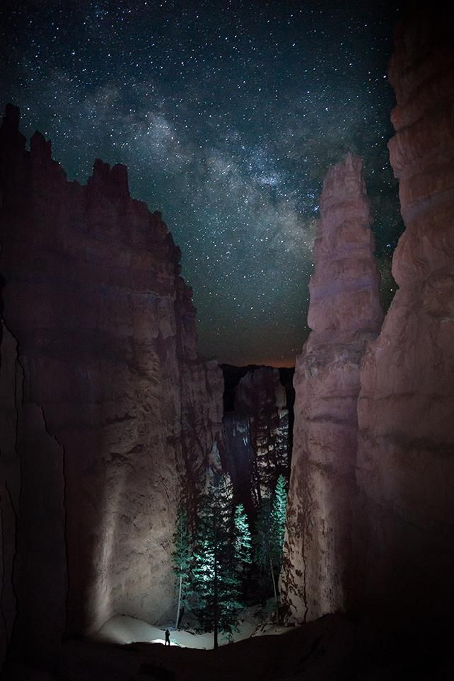 A hiker looks onto the path before him in Bryce Canyon National Park in the middle of the night as the Milky Way stretches upward above.