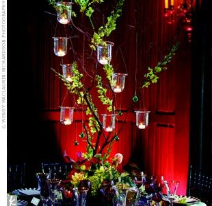 Manzanita branches rose from a base of green and purple flowers. The branches were strung with orchids, gems and candles.