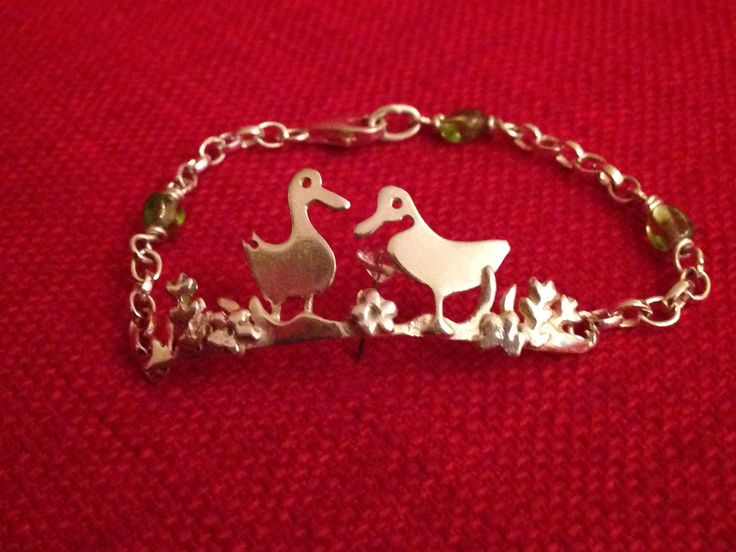 Duck bracelet hand made by Helen Green using silver sheet, silver clay, peridot beads and silver chain.