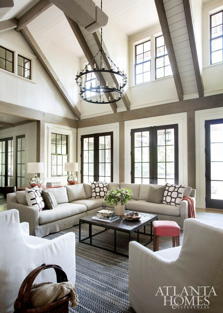 All of the living room windows face the lake, so Duffy designed the room without draperies, allowing natural light to fill every inch of the vaulted space. The chandelier is Paul Ferrante. The coffee table is Mitchell Gold + Bob Williams, the sectional is Restoration Hardware and the chairs are Lee Industries. Accent pillows are Björk Studio, the artwork is Richard Painter Studio and the rug is from Capel Rugs.
