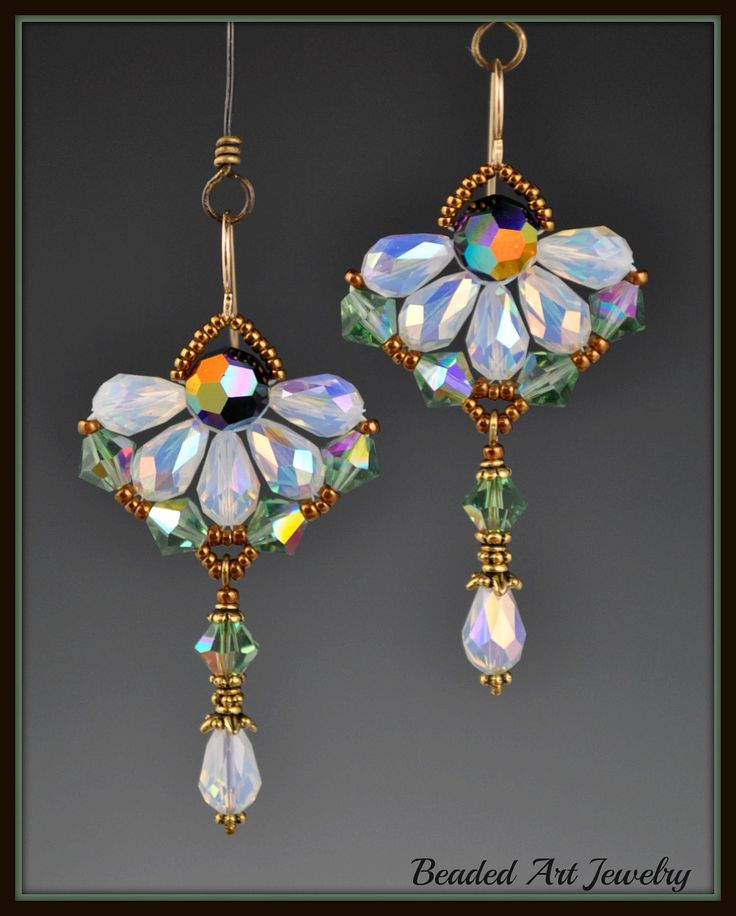 """Via Etsy: These pretty earrings are woven together to create a flower, with Swarovski 9x6 White Opal ab crystal drops and 6mm Erinite ab crystal bicones. There is an 8mm round Jet ab2x crystal in the center and the earring wires are gold filled.  They measure 2 3/8"""" long and are 1 1/4"""" wide."""