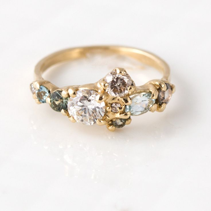 Sea Glass Cluster Ring in 14K Yellow Gold with Mossy Sapphires, Pale Blue Aquamarine, and Champagne Diamonds | Stone Cluster Engagement Ring by MelanieCaseyJewelry on Etsy https://www.etsy.com/uk/listing/269554972/sea-glass-cluster-ring-in-14k-yellow